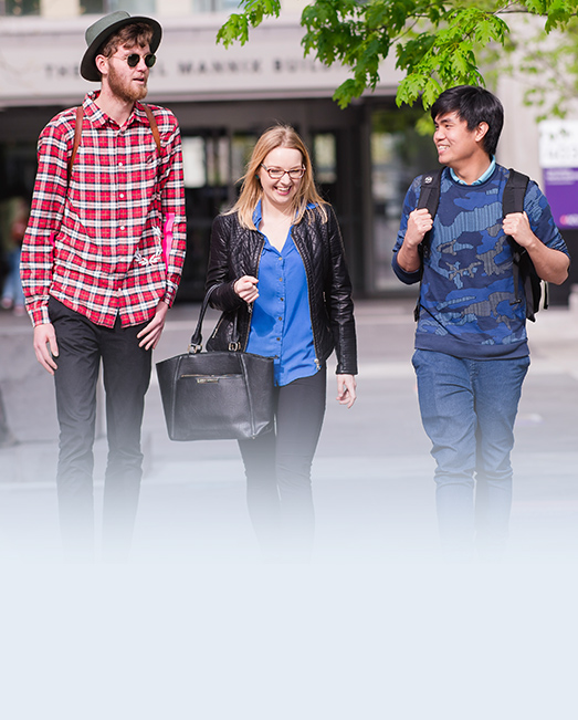 Three students walking outside ACU Melbourne Campus.