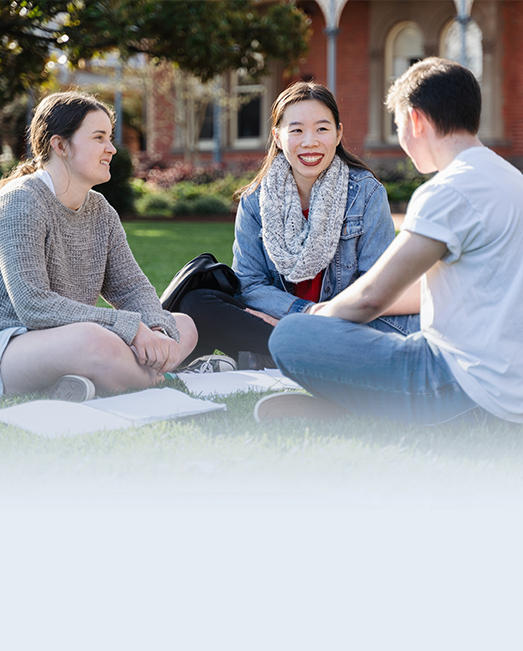 Two students sitting on the Ballarat Campus lawn