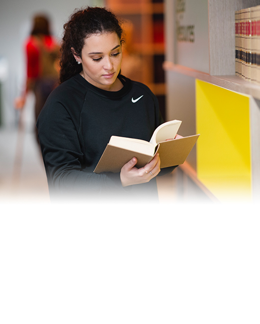 Female student standing in library reading book